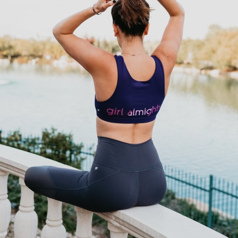 Woman sitting in workout clothes from #GirlAlmighty collection tying her hair