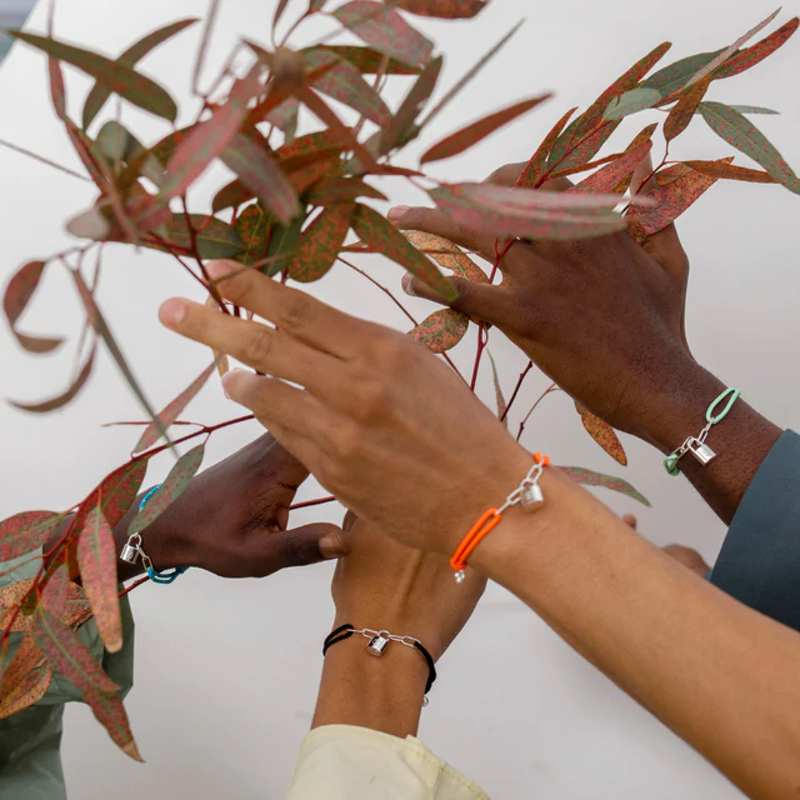 2 sets of hands holding a twill, wearing Louis Vuitton for UNICEF Silver lockit bracelets
