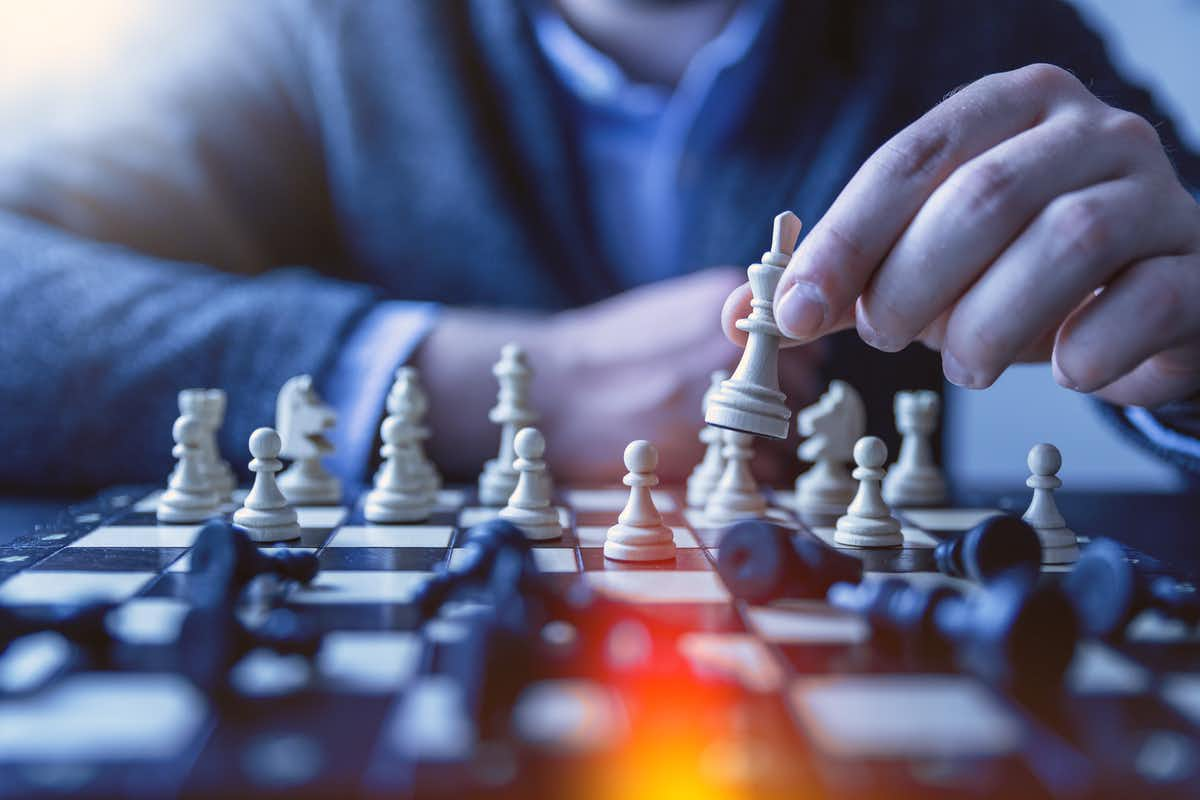 person's hand moving a chess pieces during a game