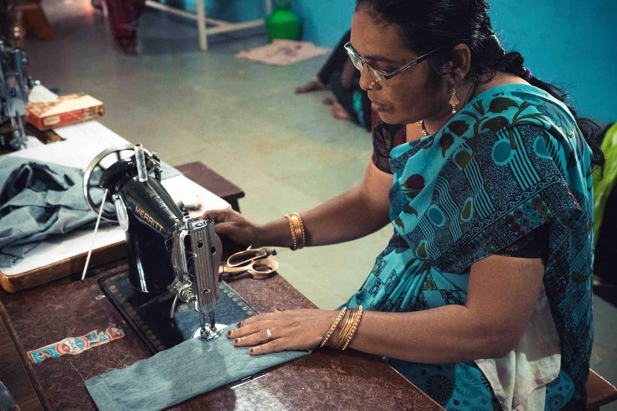 Jyoti seamstress sewing with a piece of cloth