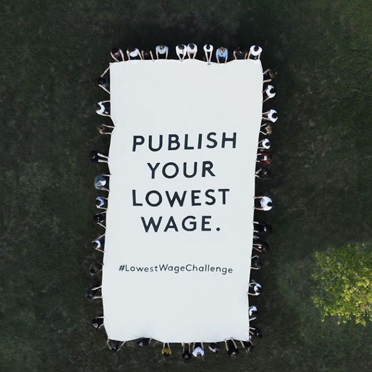 "Bird's view of people holding a large sheet that says ""Publish your lowest wage. #LowestWageChallenge"""
