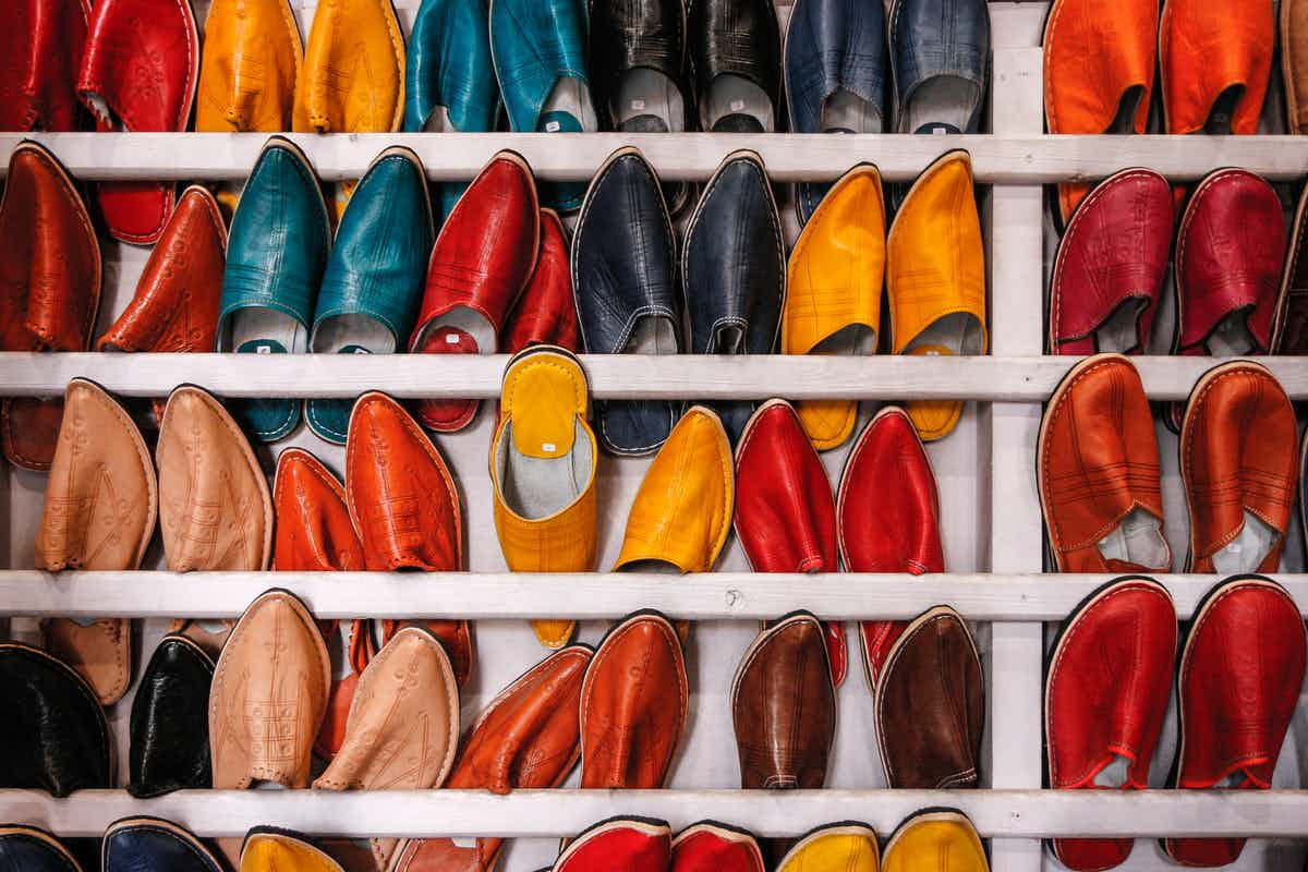a rack of vertically aligned colorful leather shoes with one shoe positioned in the opposite direction