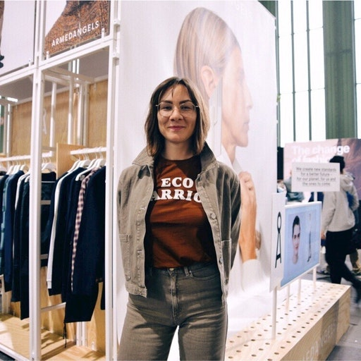 ARMEDANGLES employee Lavinia Muth standing with crossed arms in front of a mirror in a fashion store