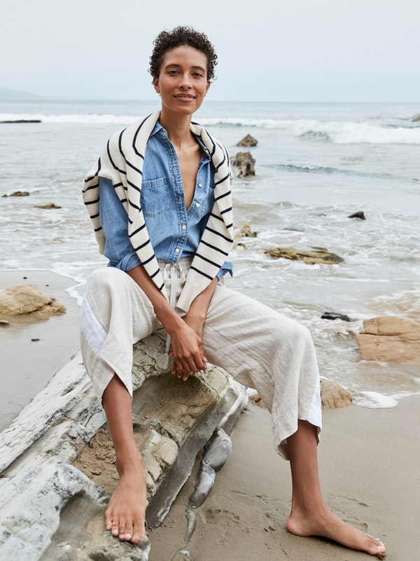 Barefoot woman sitting on the beach in J. Crew clothing
